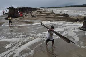 Residents recover pieces of wood after high waves dragged their beach stalls into the sea in Coyuca de Benitez